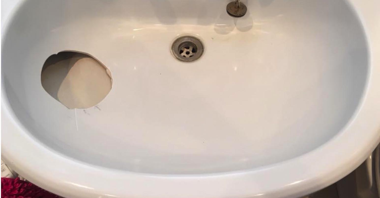 Damaged bathroom sink - Before repairing hole