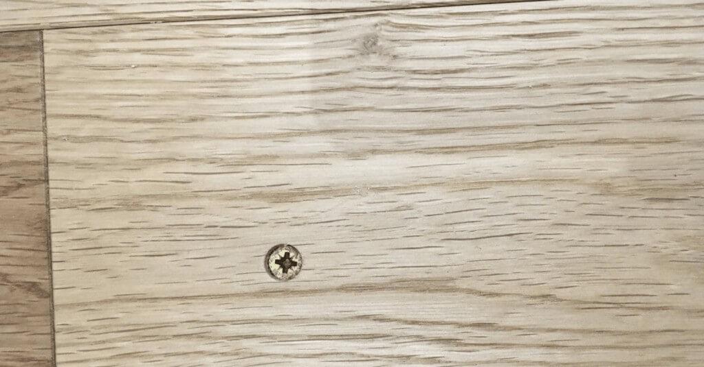 Screw showing on wooden floor - Before repair